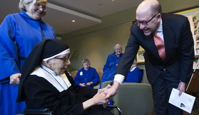 **FILE** U.S. Ambassador David Jacobson shakes hands with Sister Constance Murphy before presenting a letter of congratulations from President Obama at the Convent of Sisters of St. John the Divine in Toronto on Dec. 4, 2009. (Associated Press)
