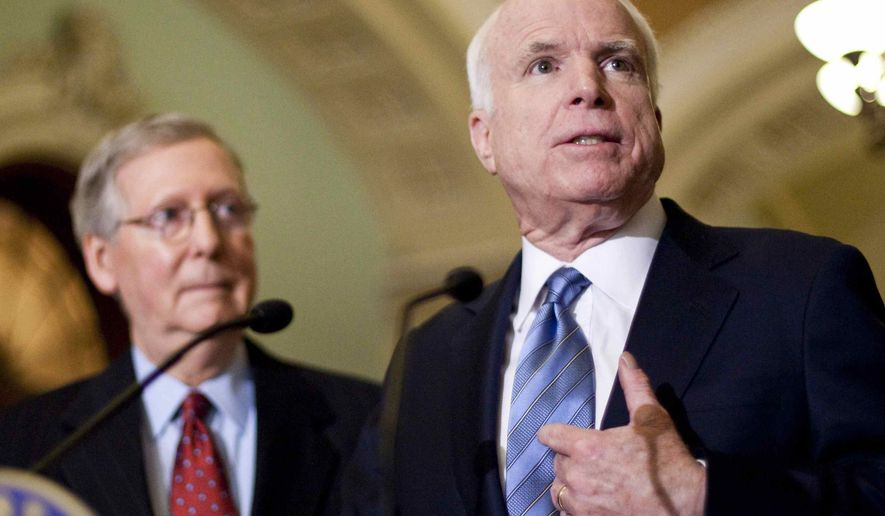 Senate Minority Leader Mitch McConnell (left), Kentucky Republican, listens as Sen. John McCain, Arizona Republican, talks to the media after the Senate Democratic caucus meeting on Capitol Hill in Washington on Sunday, Dec. 6, 2009. (AP Photo/Alex Brandon)