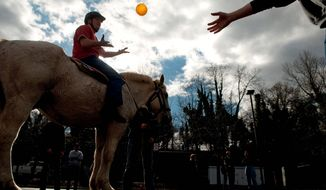 ** FILE ** Staff Sgt. Brian Isenhour is tossed a ball as he sits on his horse during a therapy session.