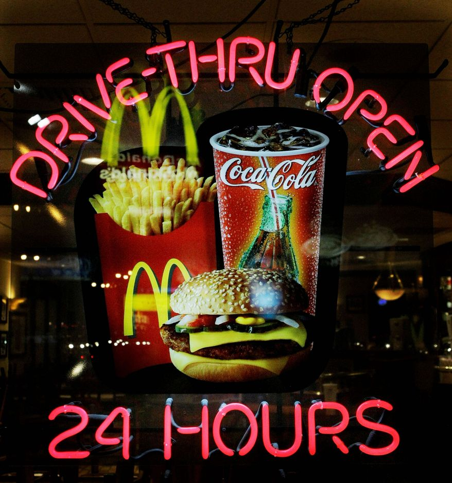 A neon sign reminds patrons at a McDonald's restaurant of the 24-hour service in the Wrigleyville neighborhood of Chicago. The fast food chain faces increased competition from rivals with their own discounted menus, such as Taco Bell's value menu and Burger King's $1 offers.