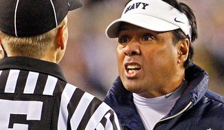 Navy head coach Ken Niumatalolo, right,  argues with an official during a college football game against Army Saturday, Dec. 12, 2009. (AP Photo/Matt Slocum)