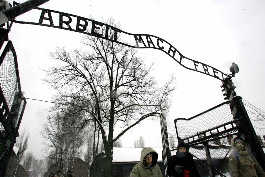 Visitors walk through the entrance gate of Nazi Germany's Auschwitz concentration camp in Oswiecim, Poland, on Jan. 26, 2005, a day before the commemoration of the 60th anniversary of the liberation of the camp by Soviet troops. (AP Photo/Herbert Knosowski)