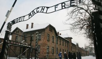 """ASSOCIATED PRESS PHOTOGRAPHS Tourists pause near the former Nazi death camp Auschwitz-Birkenau in Oswiecim, Poland, where the infamous iron sign reading """"Work Sets You Free"""" was stolen before dawn on Friday."""
