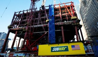 ** FILE ** A Subway sandwich shop is hoisted by crane onto the rising steel frame of One World Trade Center in New York in 2009. The concession trailer fed workers as they built the 105-floor building. (Associated Press)