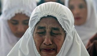 An Acehnese woman weeps during a prayer for the victims of Indian Ocean tsunami in Lhoong, Aceh province, Indonesia, Friday, Dec. 25, 2009. A giant quake in Indian Ocean on Dec. 26, 2004, triggered a massive tsunami that killed 230,000 people, half of them in Aceh. (AP Photo/Heri Juanda)