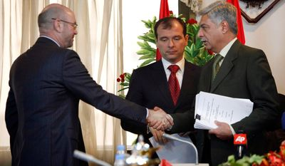 Kjetil Tonstad (left), Regional Vice President Middle East of Statoil, shakes hands with Abdul-Mehdi Al-Ami, the Deputy Director-General of the Department contracts after a signing ceremony at the Iraqi Oil Ministry in Baghdad, as Dmitry A. Timoshenko, Lukoil's vice president of strategy and business development, looks on. (Associated Press)