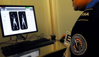 ROD LAMKEY JR./THE WASHINGTON TIMES A TSA officer views the image of a person with a cell phone using a controversial full body scanner Wednesday at the TSA Systems Integration Facility in Arlington, Va. Airports will install 150 more scanners after an attempted attack on a flight bound for Detroit on Christmas Day.