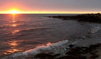 The sun rises over Nantucket Sound as seen from Popponesset Beach in Mashpee, Mass. The sacred rituals of the Wampanoag Indians require an unblocked view of it. They object to the construction of the Cape Wind project, which would obstruct the view. The National Park Service has decided the sound is eligible for protection in the National Register of Historic Places. (Associated Press)