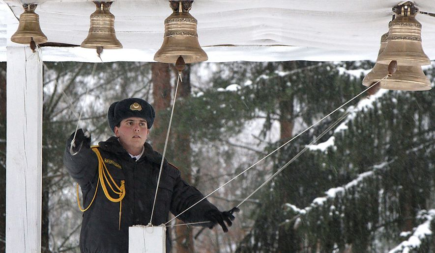 An Interior Ministry officer rings  bells at an Orthodox church before a service in the village of Okolitsa, 30 kilometers ( 19 miles) east of capital Minsk, Belarus, Thursday, Jan. 7, 2010. Belarusian Orthodox believers celebrate Christmas by the Julian calendar on Jan. 7.(AP Photo/Sergei Grits)