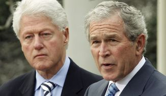 **FILE** Former President Bill Clinton (left) listens to former President George W. Bush speak on Saturday, Jan. 16, 2010, in the Rose Garden of the White House in Washington. (AP Photo/Ron Edmonds)