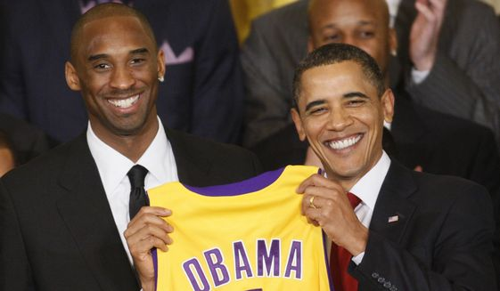 President Barack Obama holds a personalized Los Angeles Lakers team jersey presented to him by Lakers guard Kobe Bryant (left) as he honored the 2009 NBA champions Lakers in the East Room of the White House on Jan. 25, 2010. (Associated Press) ** FILE **