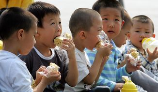 **FILE** Young boys eat their lunch during an annual kindergarten trip to Beijing's Tiananmen Square on Sept. 27, 2005. (Associated Press)