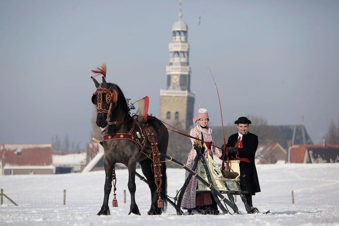A couple dressed in traditional Dutch clothes from Friesland province on a horse-drawn sled, pose for photographers in Hindeloopen, northern Netherlands, Tuesday Jan. 26, 2010, where people gathered to watch the national contest of an old form of Dutch synchronized skating. (AP Photo/Peter Dejong)