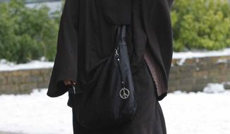 ** FILE ** Faiza Silmi, a 32-year-old Moroccan, walks in Le Mesnil-Saint-Denis, France, 24 miles southwest of Paris, on Jan. 12, 2010. (AP Photo/Christophe Ena)