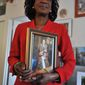 **FILE** In this Nov. 24, 2009 photo, President Obama's aunt, Zeituni Onyango, poses in her home in Boston with a framed photograph of herself and Obama when he was an Illinois state senator. (Associated Press)