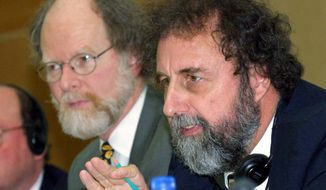 ** FILE ** In this Feb. 19, 2001, file photo, Briton Robert Watson, right, then-chairman of the Intergovernmental Panel on Climate Change (IPCC) accompanied by James J. McCarthy, USA, IPCC's co-chairman, gestures during a news conference in Geneva, Switzerland. Some climate scientists are calling for drastic changes in how future United Nations climate reports are done. (AP Photo/Donald Stampfli)