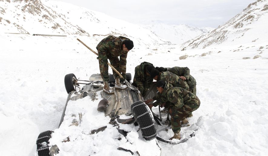 Members of Afghan army try to open the door of an overturned vehicle buried under snow at Salang Pass, some 115 kilometers (71 miles) north of Kabul, Afghanistan, Wednesday, Feb. 10, 2010. (AP Photo/Musadeq Sadeq)