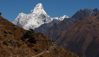 FILE - In this Dec. 3, 2009 file photo, a man walks in the backdrop of Mount Ama Dablam at Syangboche, a town in Nepal. Some climate scientists are calling for drastic changes in how future United Nations climate reports are done. (AP Photo/Gemunu Amarasinghe, File)