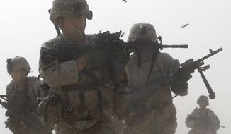 A U.S. soldier returns fire as others run for cover during a firefight with insurgents in the Badula Qulp area, West of Lashkar Gah  in Helmand province, southern Afghanistan, Sunday, Feb. 14, 2010.  The area is near Marjah, where U.S. Marines are conducting an offensive against the Taliban. (AP Photo/Pier Paolo Cito)