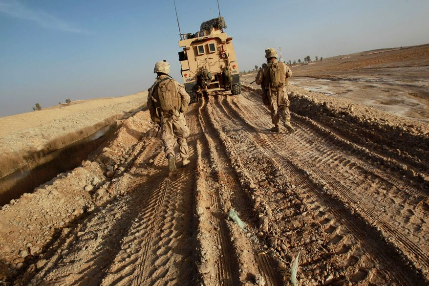 U.S. Marines walk on tracks of a vehicle to avoid improvised explosive devices (IEDs) as their platoon clears a route to reach another platoon in Marjah in Afghanistan's Helmand province in 2010. Marines airdropped into the region came under intense Taliban fire. (Associated Press)