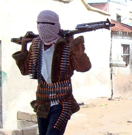 **FILE** A Somali Islamist militant patrols the streets of Mogadishu. Al-Shabab Islamic insurgents, with links to al Qaeda, last year looted two United Nations compounds in southern Somalia. The Somali capital sees almost daily attacks aimed at disrupting the weak government. (Associated Press)