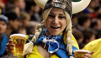 A fan of the Swedish team carries beverages in the second period of a preliminary round men's ice hockey game between Sweden and Finland at the Vancouver 2010 Olympics in Vancouver, British Columbia, Sunday, Feb. 21, 2010. (AP Photo/Julie Jacobson)