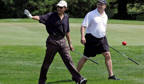 ** FILE ** President Obama gets a round of golf in with hospital executive Eric Whitaker during the president's vacation on Martha's Vineyard in Oak Bluffs, Mass., in August. Mr. Whitaker, whom he met years ago at Harvard, is one of the president's best friends. (Associated Press)