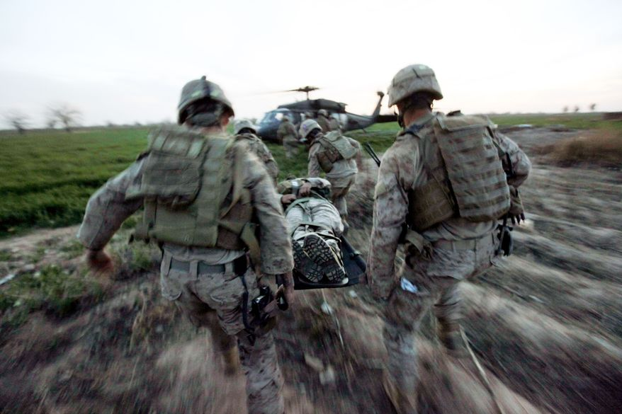 Marines carry a wounded comrade to a waiting helicopter after an improvised explosive device detonated near their armored vehicle in the Taliban stronghold of Marjah in Afghanistan's Helmand province on Tuesday. (Associated Press)