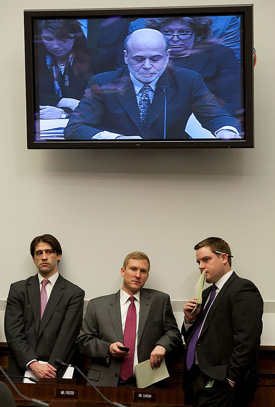 """Congressional aides stand under a monitor as Ben S. Bernanke, chairman of the U.S. Federal Reserve, gives his semiannual monetary report to the House Financial Service Committee in Washington on Feb. 24, 2010. Bernanke said the U.S. economy is in a """"nascent"""" recovery that still requires low interest rates to encourage demand by consumers and businesses once federal stimulus expires. (Joshua Roberts/Bloomberg)"""