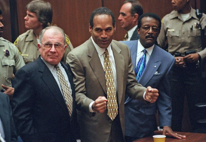 **FILE** In this Oct. 3, 1995, photo, O.J. Simpson (center) reacts as he is found not guilty of murdering his ex-wife, Nicole Brown, and her friend Ronald Goldman, as members of his defense team, F. Lee Bailey (left) and Johnnie Cochran Jr., look on in court in Los Angeles. (Associated Press)