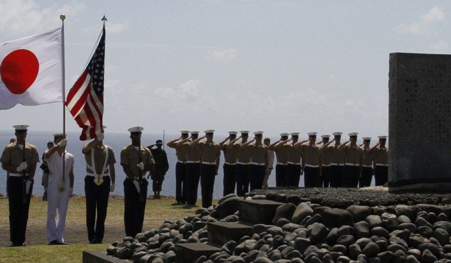 The color guard holds the flags of Japan and the U.S. during a ceremony commemorating the 65th anniversary of the Battle of Iwo Jima on Iwo Jima, Japan, on Wednesday. Dozens of U.S. veterans, now in their 80s and 90s, returned to the remote volcanic island to mark the 65th anniversary of one of World War II's fiercest battles. (Associated Press)