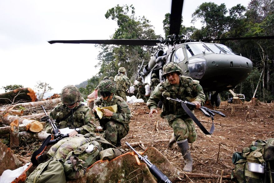 **FILE** Colombian army soldiers unload supplies from a helicopter during a February operation to relieve troops in Alto Guaduas, Caqueta state, in southern Colombia, a region with a strong presence of the Revolutionary Armed Forces of Colombia. (Associated Press)