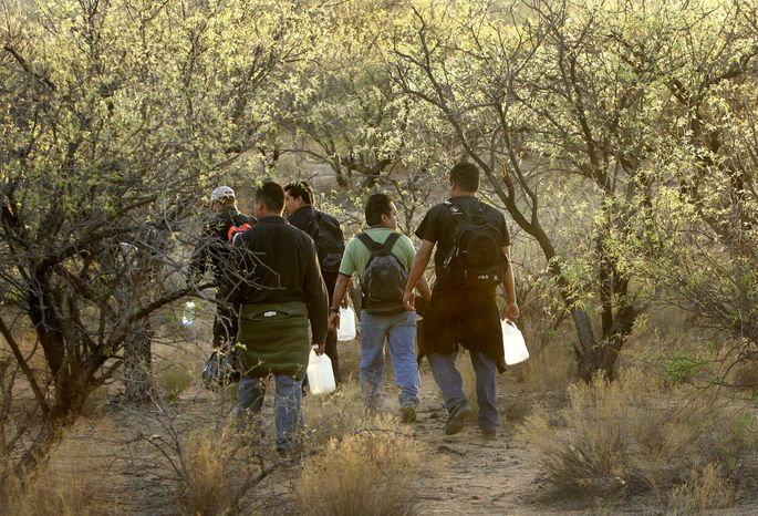 A group of illegal immigrants walk with bottles of water shortly before nightfall as they cross the desert between Sasabe, Mexico, and Sasabe, Ariz., in April 2006. (Associated Press)