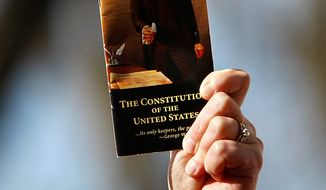 In this file photo, a rally participant holds up a pocket-sized copy of the U.S. Constitution during an anti-health-care-reform rally by The American Grassroots Coalition and The Tea Party Express on Capitol Hill in Washington, Tuesday, March 16, 2010. (AP Photo/Gerald Herbert)