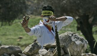 A Palestinian demonstrator uses a slingshot to hurl stones at Israeli soldiers, not seen, during clashes in the West Bank village of Iraq Burin, near Nablus, Saturday, March 20, 2010. A Palestinian teenager was killed during clashes with Israeli troops in Iraq Burin, medical officials said. (AP Photo/Nasser Ishtayeh)