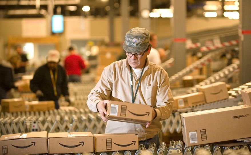**FILE** An Amazon.com employee grabs boxes off the conveyor belt for shipment at a Fernley, Nev., warehouse. (Associated Press)