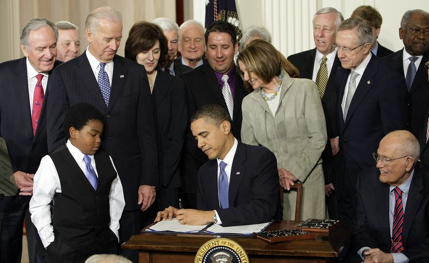 ** FILE ** Marcelas Owens (foreground left) of Seattle, Rep. John Dingell (seated at right) and others look on as President Obama signs the heath care reform bill in the East Room of the White House in Washington on Tuesday, March 23, 2010. (AP Photo/J. Scott Applewhite)