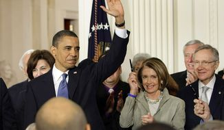 President Obama waves in the East Room of the White House after signing the health care bill on Tuesday. From left: Vicki Kennedy, widow of Sen. Edward Kennedy; the president; House Speaker Nancy Pelosi of Calif.; House Majority Leader Steny Hoyer of Md.; and Senate Majority Leader Harry Reid of Nev. (Associated Press)
