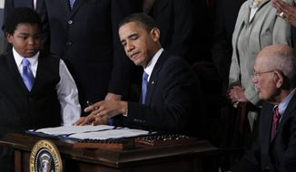 ** FILE ** President Obama signs the health care reform bill in the East Room of the White House in Washington on March 23, 2010, as Marcelas Owens (left), 11, of Seattle and Rep. John D. Dingell (right), Michigan Democrat, look on. (AP Photo/Charles Dharapak)