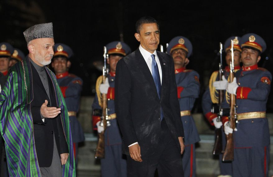 ** FILE ** President Obama reviews the honor guard with Afghan President Hamid Karzai (left) at the presidential palace in Kabul, Afghanistan, during Mr. Obama's unannounced visit on Sunday, March 28, 2010. (AP Photo/Charles Dharapak)