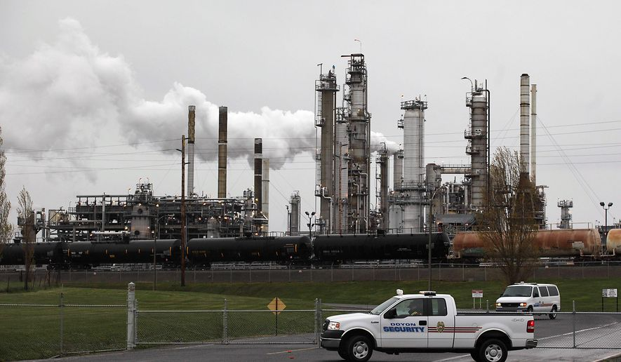 Security vehicles are shown at a gate to a Tesoro Corp. refinery , Friday, April 2, 2010, in Anacortes, Wash. An overnight fire and explosion at the refinery killed at least three people working at the plant. (AP Photo/Ted S. Warren)
