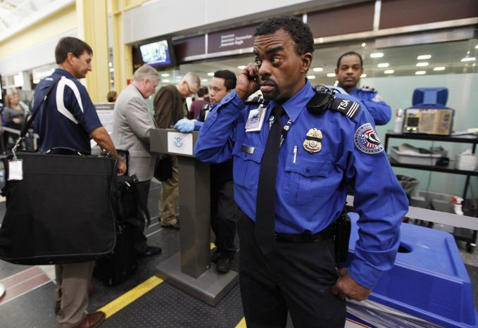 **FILE**Transportation Security Administration's Behavior Detection Officer Terrence McClain (right) watches United Airlines passengers checking in for the morning flight at Washington's Ronald Reagan Washington National Airport on April 8, 2010. (Associated Press)