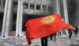A protester covered by Kyrgyz national flag walks April 8, 2010, in front of Kyrgyz government headquarters on the central square in Bishkek, Kyrgyzstan. (Associated Press)