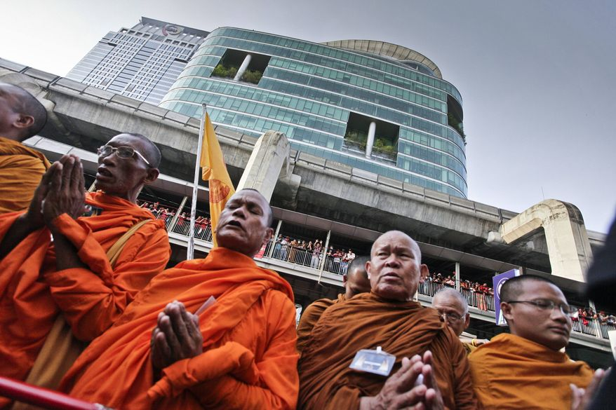 ** FILE ** Thai Buddhist monks pray for peace as anti-government demonstrators gather to shout insults at police outside police headquarters on Friday, April 9, 2010, in Bangkok. (AP Photo/David Longstreath)