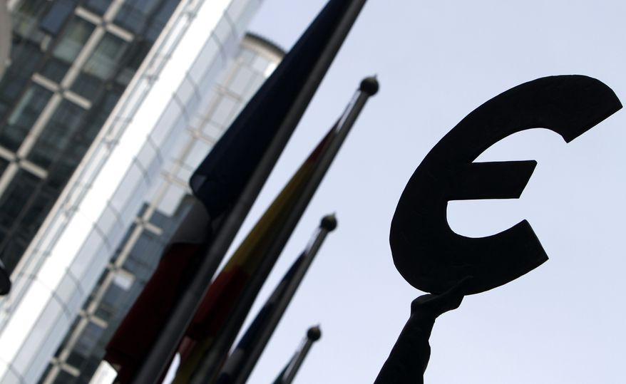 The euro symbol sits atop a statue at the European Parliament in Brussels. (AP Photo/Virginia Mayo) ** FILE **