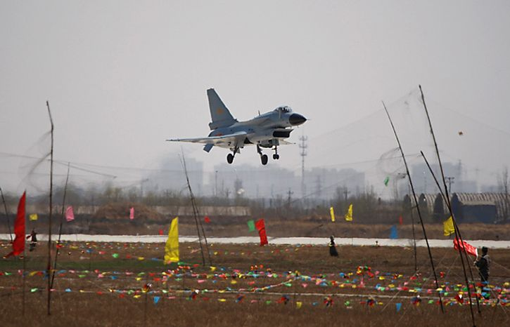 """A Chinese People's Liberation Army Airforce's """"Bayi Aerobatic Unit"""" J-10 fighter jet lowers its landing gears during an aerial demonstration at a base of the PLA Airforce's 24th Division in Yangcun, Tianjin, China, Tuesday, April 13, 2010. The media, along with about 51 military attaches from embassies in Beijing, including the United States, Britain and Israel, witnessed a 15-minute demonstration by four pilots from the 24th Air Division in China's domestically developed J-10 fighters. (AP Photo/Alexander F. Yuan)"""