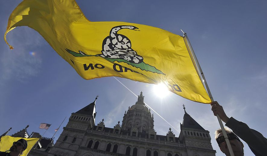 Scott Veley of Kensington, Conn., holds a Gadsden flag during a tea party protest at the Capitol in Hartford, Conn., on April 15, 2010. (Associated Press) ** FILE **