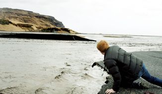 A man looks at a broken section of Iceland's main coastal ring road near Reykjavik on after a volcanic eruption caused ice to melt and river levels to rise by up to 10 feet. (Associated Press) ** FILE **