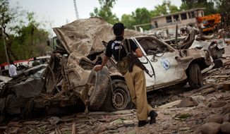 **FILE** A Pakistani police officer guards a U.N. car destroyed in June 2009 by suicide bomber at the Peshawar Pearl Continental Hotel. An increase in terrorist attacks in Pakistan and Afghanistan triggered a spike in the number of civilians killed or wounded in 2009, pushing South Asia past the Middle East as the top terror region in the world, according to new figures compiled by a U.S. intelligence agency. (Associated Press)