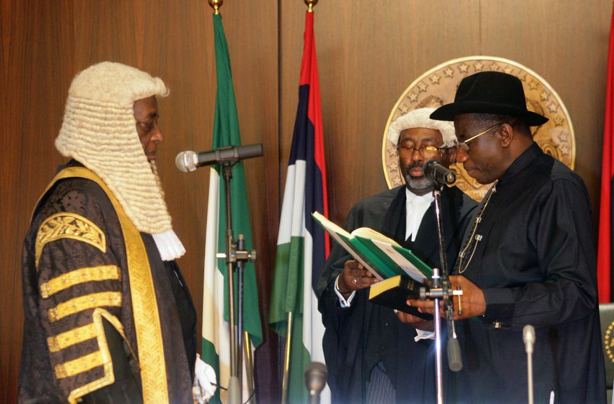 ** FILE ** Nigeria's acting president, Goodluck Jonathan (right), takes the oath of office in front of Chief Justice Aloysius Katsina-Alu (left) to become the nation's next leader, at the presidential villa in Abuja, Nigeria, on Thursday, May 6, 2010. Mr. Jonathan was sworn in just hours after the death of the oil-rich country's elected leader, whose long illness had sparked a leadership crisis. (AP Photo)
